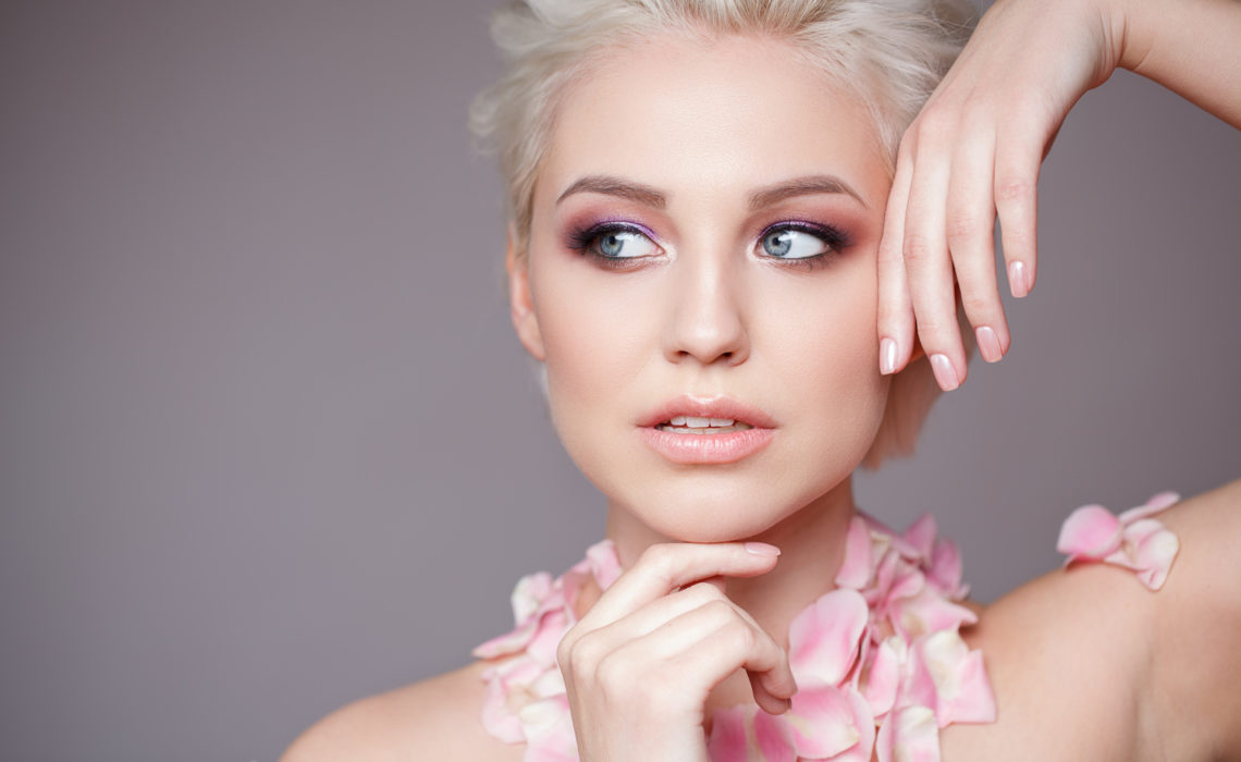 Photo of a beautiful blond woman with flower. Closeup attractive sensual face of white woman with curly hair. Smokey eye makeup. Studio